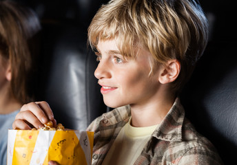 Boy Eating Popcorn While Watching Movie