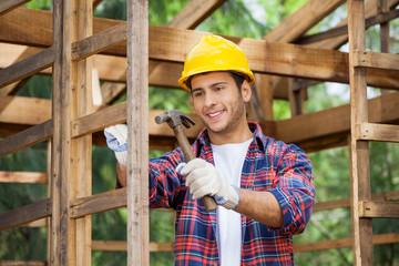 Worker Hammering Nail On Wooden Cabin