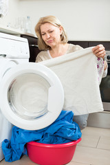 Elderly woman cheking white clothes