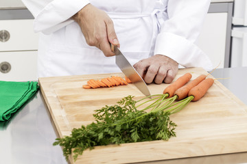 Slicing carrots in kitchen