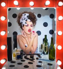 Девушка возле зеркала делает себе макияж.