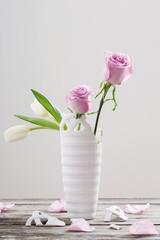 pink roses in broken  vase on old wooden table