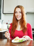 long-haired woman eating potatoes