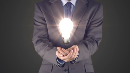 Businessman presenting light bulb with hands
