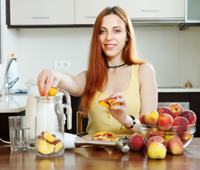 Positive woman cooking  beverages  from peaches