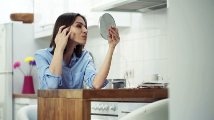 Woman checking her face in the mirror sitting in kitchen