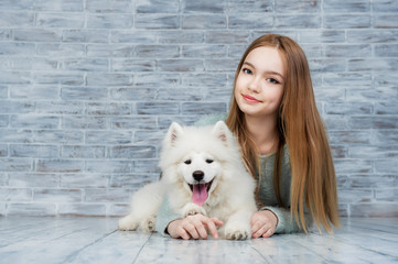 Beautiful girl huging Samoyed dog