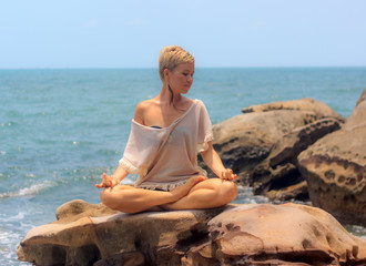 Beautiful woman seated in yoga pose at blue sea background