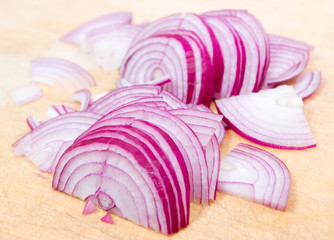 Cuts of red onion on a wooden board