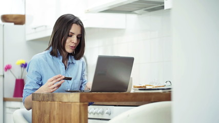 Young woman doing online shopping with laptop in kitchen