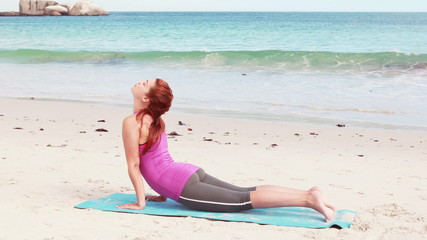 Woman stretching her body on the beach