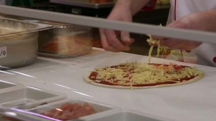 Hand chef preparing puts cheeze, ham on a pizza