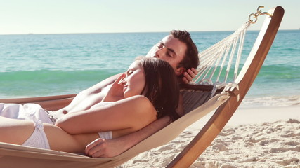 Couple relaxing in hammock at the beach