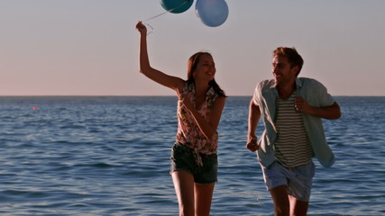 Happy friends running with balloons