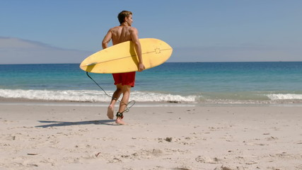 Handsome man running in the water with surfboard