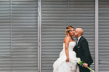 The Happy Pair Kissing Besides a Metallic Door Outdoors
