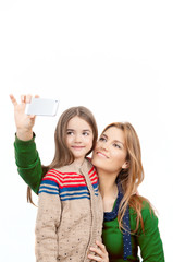 Portrait of cheerful daughter and mother using mobile phone to t