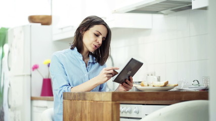Young woman doing online shopping with tablet computer in kitche