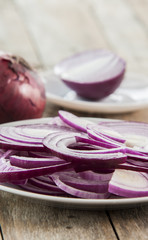 Sliced red onion on white plate close up