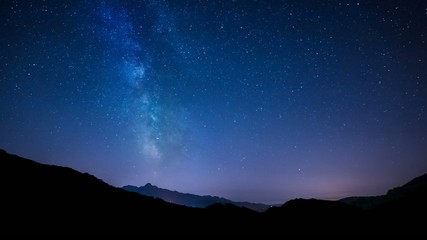 timelapse night sky stars milky way on mountains background.