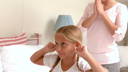 Upset little girl covering her ears while her mother screaming