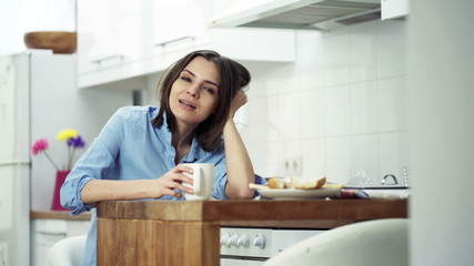 pretty woman talking to camera, sitting by table in kitchen