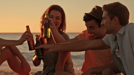 Friends drinking beer at the beach