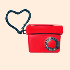Red old retro rotary phone with heart shape of wire, vintage col