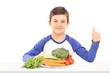 Boy sitting behind a plate full of fresh vegetables