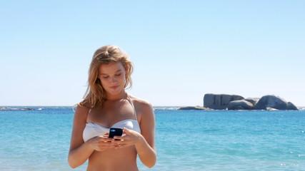 Beautiful blonde taking selfie on beach