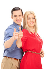 Young couple posing sideways and giving thumbs up