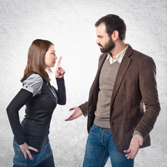 Young girl making silence gesture at her boyfriend over white ba