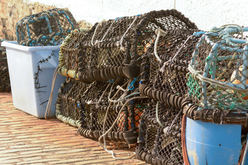 Lobster pots stacked on harbour wall