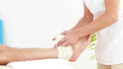 Physiotherapist wrapping injured ankle in bandage