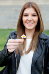 Pretty cool girl offering a beautiful flower