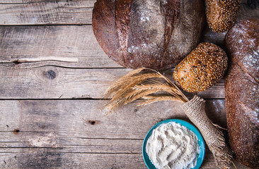 Rustic breads, wheat and flour on wooden background