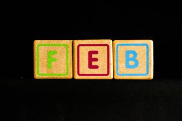 February on wood Cubic on black background
