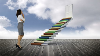 Businesswoman looking at stair made of books on a wood ground