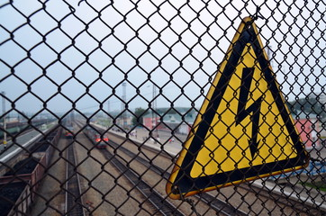 """warning sign """"attention!high voltage"""" on a metal fence"""