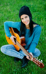 Young brunette girl playing guitar
