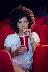 Young woman watching a film and drinking a soda