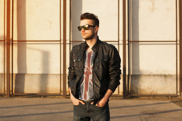 Portrait of a young man in a black leather jacket and sunglasses