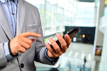 Business Man using Mobile Cell Phone in The Modern office buildi