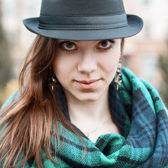Portrait of a cute girl with a hat and a scarf.