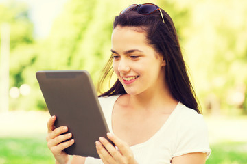 smiling young girl with tablet pc sitting on grass