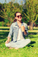 smiling young girl with cup of coffee in park