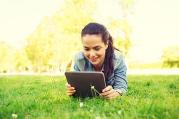 smiling young girl tablet pc lying on grass