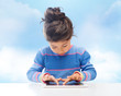 little girl with tablet pc over sky background