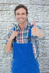 Image of confident plumber holding tool