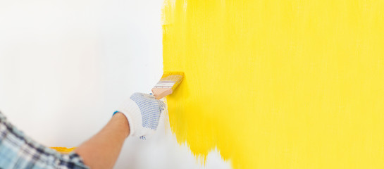 close up of male in gloves painting a wall